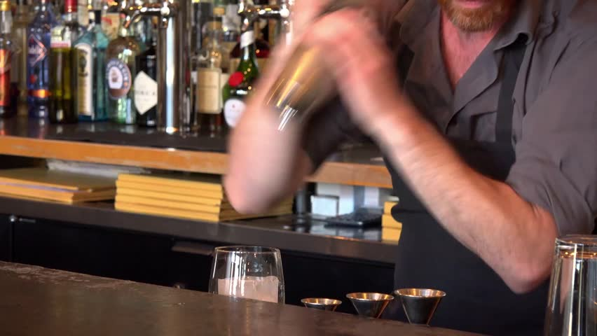 A mixologist prepares a drink at a