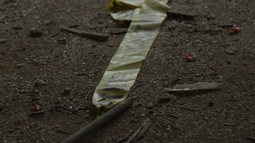 Yellow Caution Tape Strewn Across Messy Floor with Building Debris