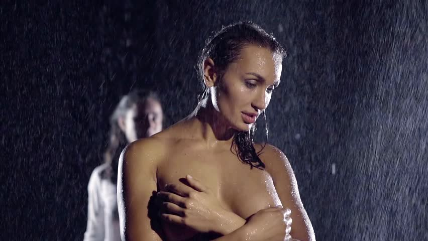 insanely beautiful sexy girl standing naked under a big rain, she covers her big Tits with his hands. her lover comes up behind her and takes over wet shoulders.