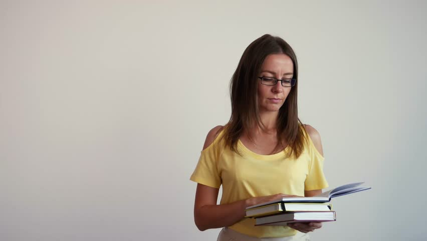 A girl closes a book and holds books in hands. Young woman in strict glasses looks into the camera. Female student holding books and smiling.   | Shutterstock HD Video #28948819