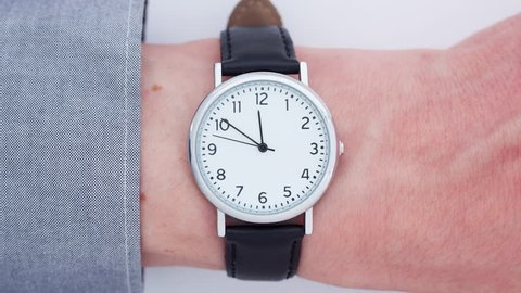 Close up time-lapse of a wrist watch on a Caucasian man`s wrist approaching 12 o' clock themes of deadline appointment late departure