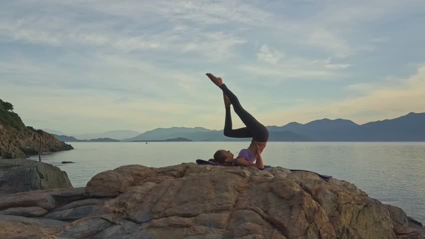 drone view girl bends knee lying in yoga pose Sarvangasana against pictorial green hilly coast at sunrise