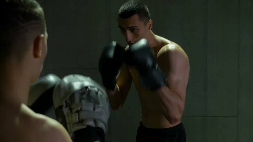 Two sweaty kickboxer boxers sparring and fighting at the gym