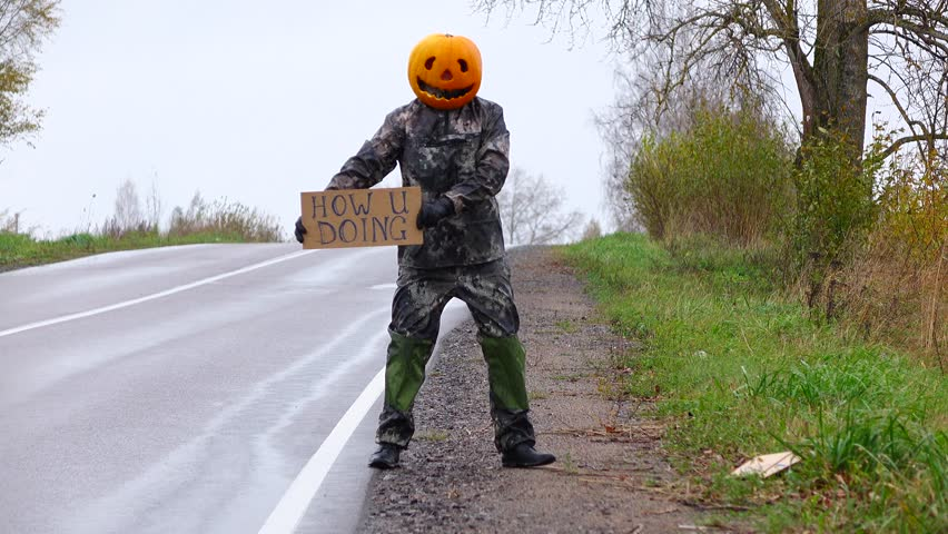 Man with carved pumpkin on head play prank at rural road, thumbing and show 'How U Doing' cardboard sign. Jack Pumpkinhead stay at empty country road side, hitchhiking