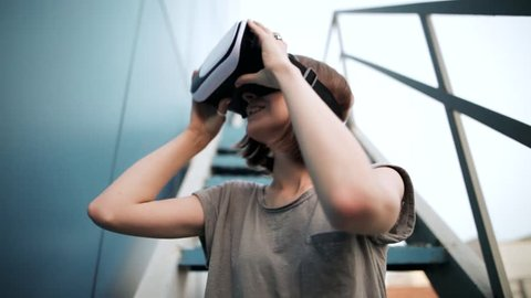 Closeup of Young girl with a small hands holding virtual reality glasses on a blue background in the evening. Blue background. Future is now. VR concept. Female wearing futuristic VR box headset.