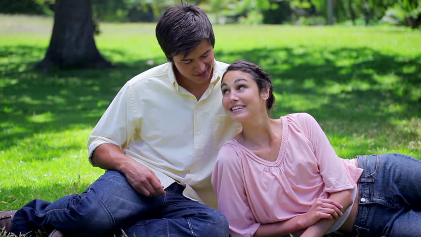 Smiling woman reading a book while lying next to her boyfriend in a parkland #2899228