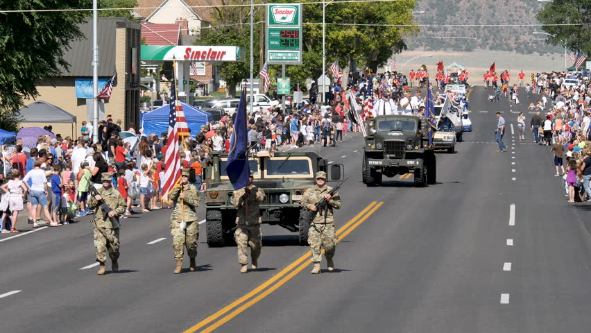 MORONI, UTAH-JULY 4, 2017:Crowds line the Main Street of a small town USA as National Guard members march US and Utah state flag starting annual 4th of July Parade kicking off the holiday celebrations