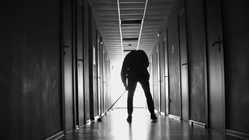 PAN with rear view of silhouette of male janitor sweeping floor in dark hallway lit by natural lighting coming from only window | Shutterstock HD Video #28998088