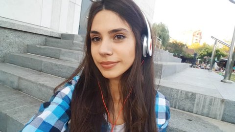 Cute girl with headphones and skateboard wearing plaid shirt and denim shorts is taking selfies with her mobile phone. Selfie video.
