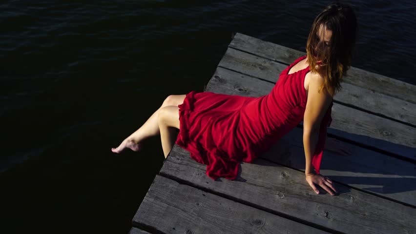 Young brunette Caucasian woman wearing elegant red dress is sitting on the edge of a wooden jetty on a lake on a sunny summer afternoon. High contrast shot. | Shutterstock HD Video #29003428