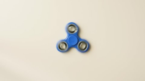 Fidget spinner isolated over white background with spinning motion blur and rotation trails. Top view.