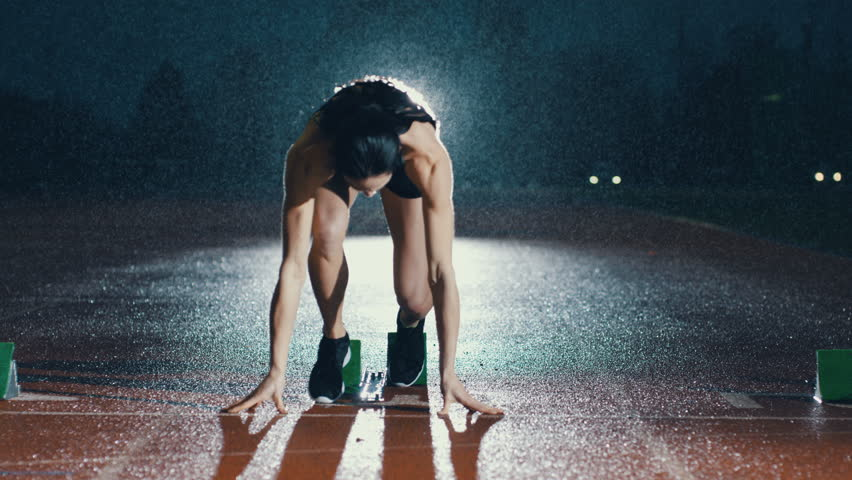 Female athlete training at running track in the dark & in the rain. Slow motion. | Shutterstock HD Video #29016898