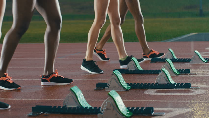 Female runners at athletics track crouching at the starting blocks before a race. In slow motion.