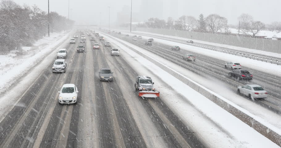 Cars driving in traffic on a snow covered road during a winter blizzard