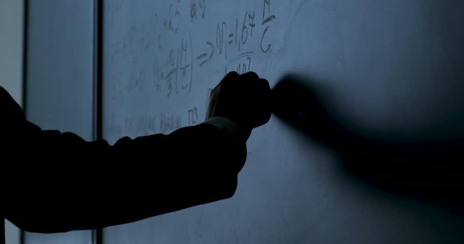 Scientist writing formulas on chalkboard. Hand with chalk wrote physics formulas on black chalkboard closeup | Shutterstock HD Video #29025940