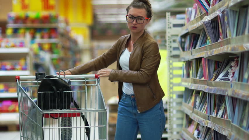 Young beautiful woman buying stationery for school, beautiful mother choose tools in a supermarket for her children, student shopping in a supermarket | Shutterstock HD Video #29051284
