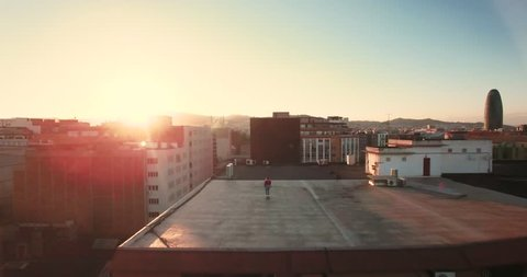 Aerial, scenic and dramatic shot of tiny small teenager girl is skating on her longboard on rooftop at sunset, drone flies toward and away to show industrial gentified district at summer evening