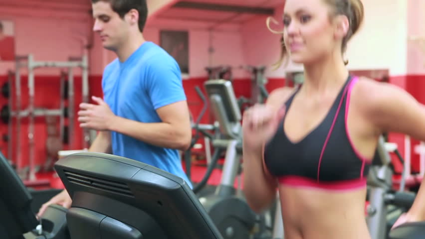 Woman and man running on a treadmill in gym