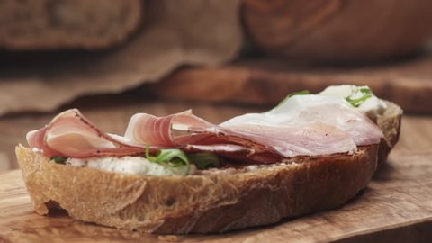 Slow motion of italian speck put on rustic bread with arugula and ricotta cheese