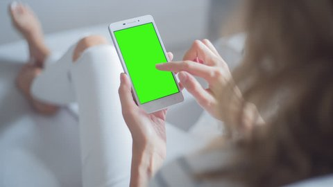 Young Woman in white jeans sitting on couch uses SmartPhone with pre-keyed green screen. Few types of gestures - scrolling up and down, tapping, zoom in and out.