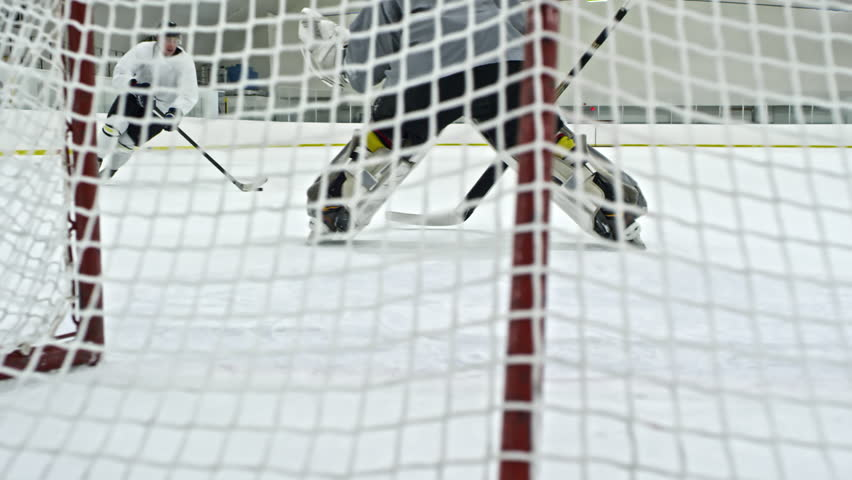 Slow Motion Shot Behind Net Of Hockey Goalie Tracking Puck And