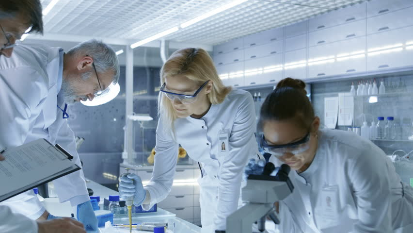 Team of Medical Research Scientists Work on a New Generation Disease Cure. They use Microscope, Test Tubes, Micropipette and Writing Down Analysis Results. Laboratory Looks Busy, Bright and Modern. 4K | Shutterstock HD Video #29108968