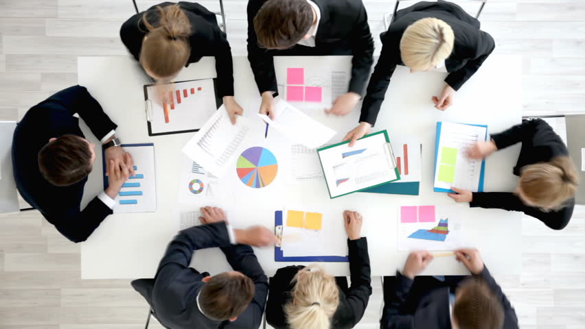 Business people work with statistics documents with tables and diagrams sitting around the table | Shutterstock HD Video #29115700
