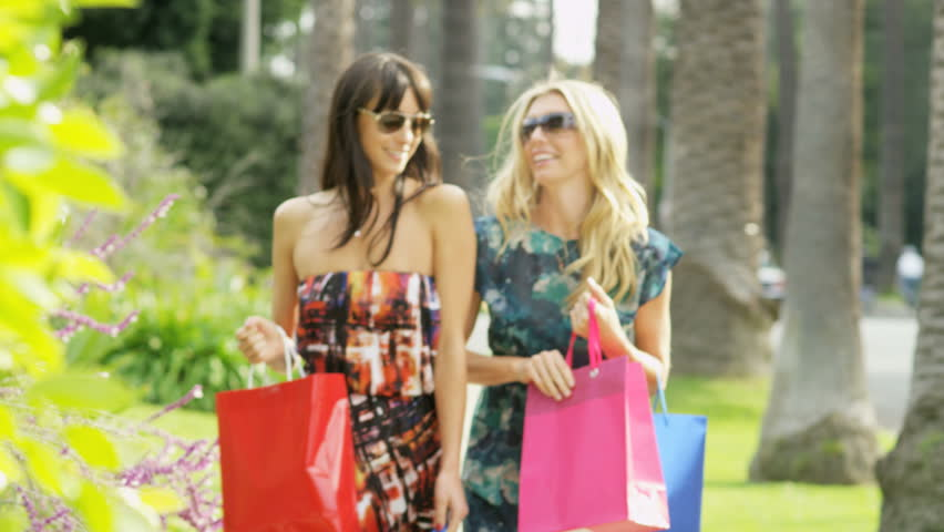 Beautiful tanned young European female friends returning with bags of designer fashion after successful shopping trip RED EPIC | Shutterstock HD Video #29120938