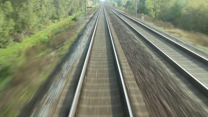 train passing through countryside, moving railroad tracks