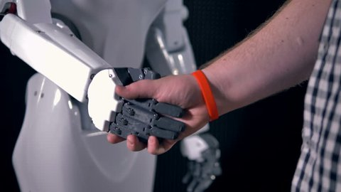 Robotic and human hands join in a handshake.