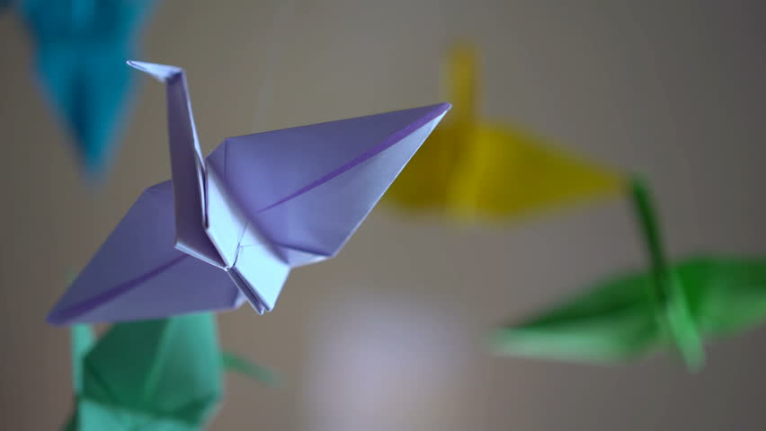 Violet origami crane bird spinning by thread, imagination, relaxing background | Shutterstock HD Video #29132398