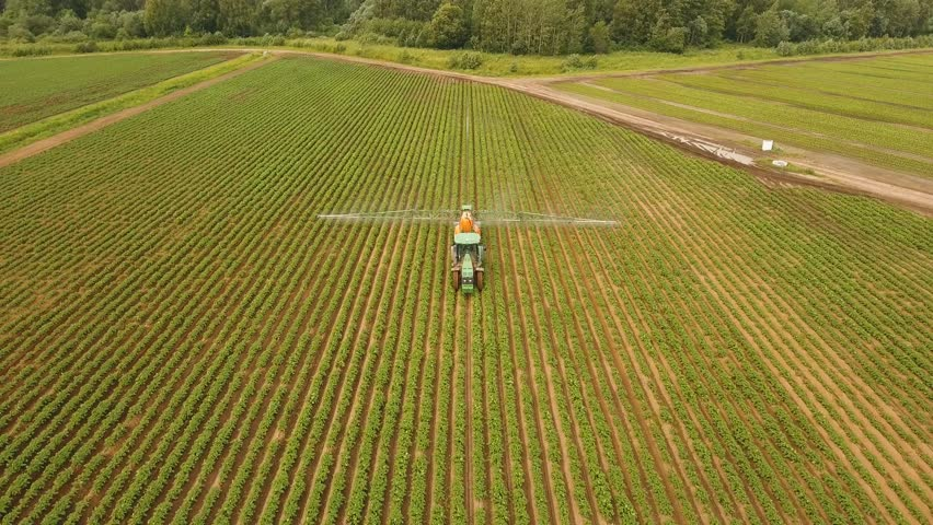 Aerial view tractor spraying the chemicals on the large green field. Spraying the herbicides on the farm land. Treatment of crops against weeds. 4K, aerial footage. #29144038