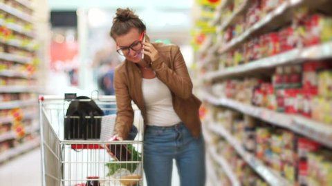 A young modern girl is shopping at a supermarket and talking on her cell phone. Sincere smile. The supermarket cart is full of products