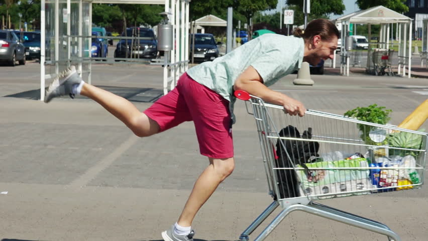A young man is riding a trolley in a parking lot near a supermarket. The basket is full of products. Fun and good mood. Merry shopping. Dad buys food