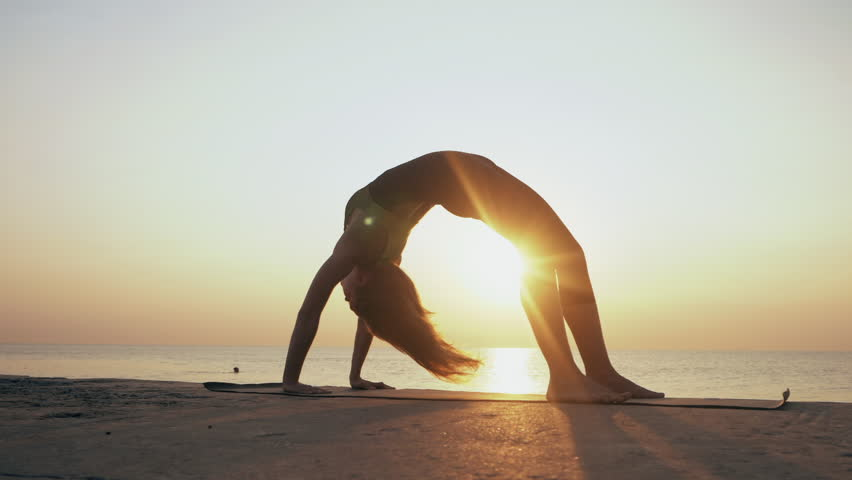 Young woman in bodysuit practicing yoga on the beach above sea at amazing sunrise. Fitness, sport, yoga and healthy lifestyle concept. Girl doing a bridge, Slow motion. | Shutterstock HD Video #29186428