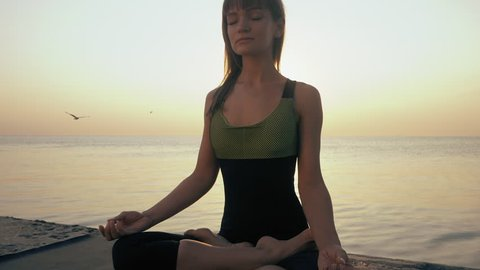 Young caucasian woman in bodysuit relaxing by practicing yoga on the beach near calm sea, close-up of hands, gyan mudra and lotus position. Sunrise background. Slow motion.