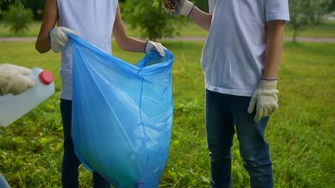 Attentive young volunteers cooperating while keeping park clean