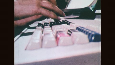 1970s: Fingers typing on keyboards. Woman works on early computer.