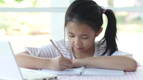 Beautiful asian girl thinking and writing to notebook on the table slow motion