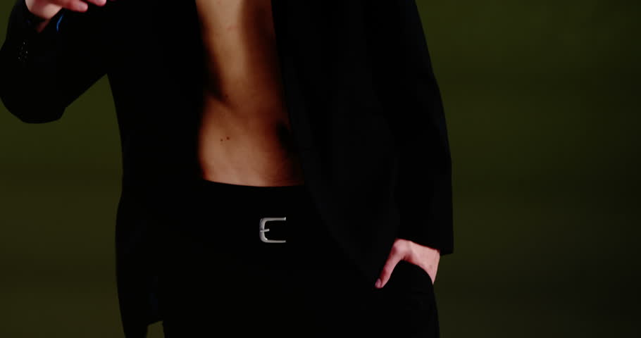 Confident androgynous man in blazer posing against black background