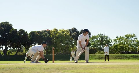 Caucasian batsman hitting a ball during match on cricket field