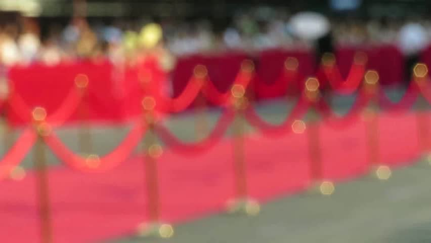 Blurred video. Red carpet entrance with golden stanchions and ropes. Celebrity nominees go to the premiere. Stars on the festive awarding of prizes awards