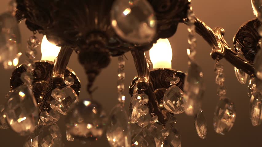 Brilliant crystal chandelier hanging on ceiling. Close up large classical crystal chandelier. Luxurious crystal chandelier. Vintage crystal chandelier in a luxurious interior