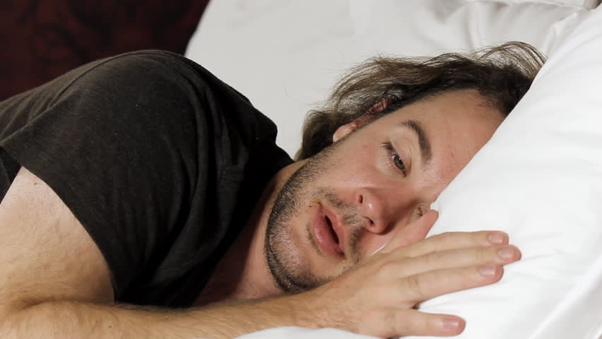 Man has trouble falling asleep tosses and turns in bed - Fast motion