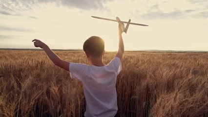 Happy child runs with a toy airplane on a sunset background over a wheat field