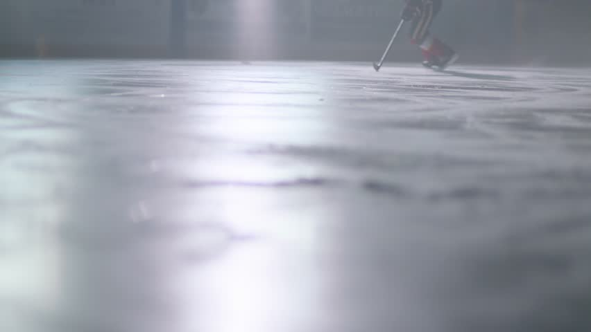 Ice hockey stick handling player skating skates in an arena in slow motion and stopping abruptly