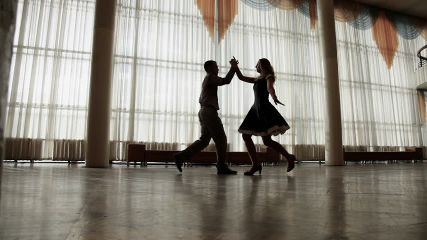 Attractive couple training to dance together. Silhouettes. Dolly shot.