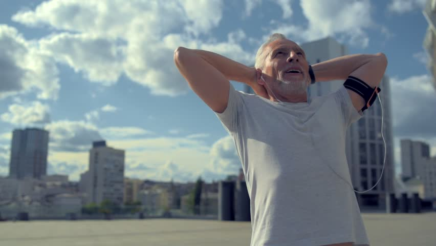 Joyful aged man enjoying sport in the city