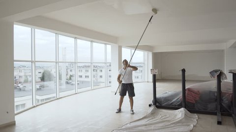 Ethnic worker painting walls in a hall with roller, camera on glidecam moving around