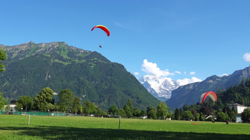INTERLAKEN, SWITZERLAND: Paragliders in front of the Alps in Interlaken, Switzerland. Interlaken is a resort town in the Interlaken-Oberhasli administrative district in the Swiss canton of Bern.